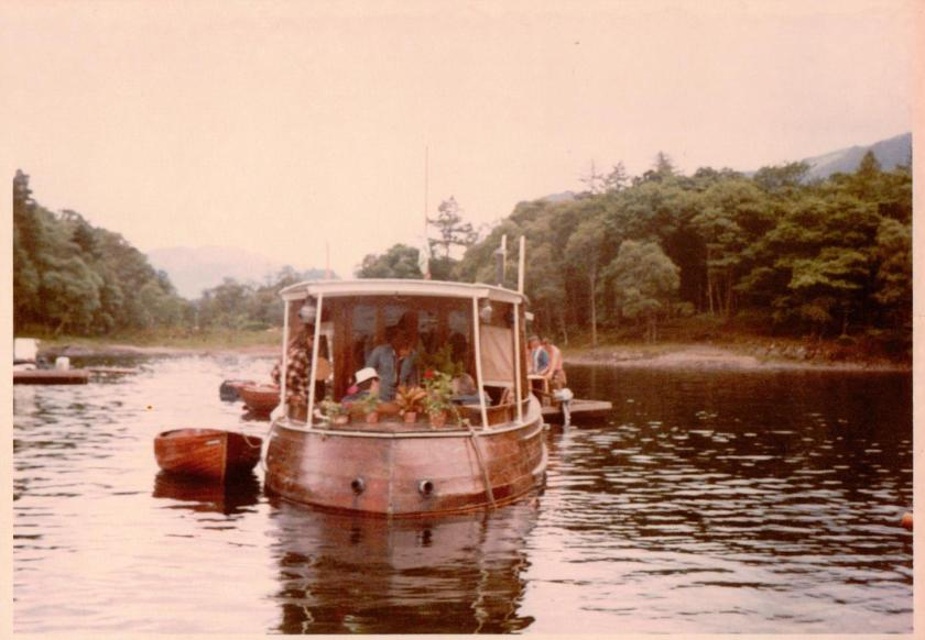 Claude Whatham discussing plans with sailing director David Blagden (in the white hat) and Richard Pilbrow on the aft deck of the houseboat with Molly Pilbrow looking on ~ photo: Daphne Neville