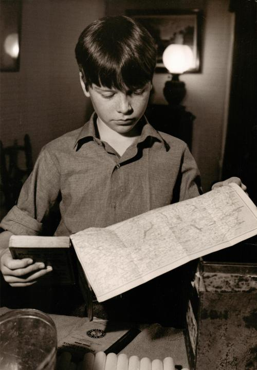 Simon West as John Walker studying the chart at Holly Howe before the voyage.