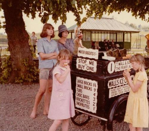 Tamzin in pink and and Perry in yellow eating ice creams whilst appearing as film extras in 'Swallows & Amazons'. Kit Seymour and Jane Grendon stand behind them.